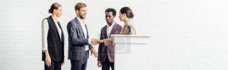 Photo pour Tir panoramique de quatre collègues multiethniques en tenue formelle parler et se serrer la main - image libre de droit