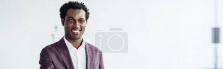 Photo pour Tir panoramique de l'homme d'affaires américain africain dans l'usure formelle souriant dans le bureau - image libre de droit