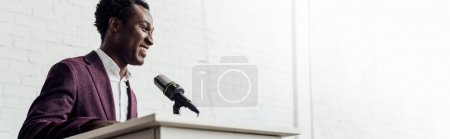 Photo for Panoramic shot of panoramic shot of african american businessman in formal wear talking during conference - Royalty Free Image
