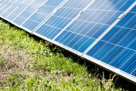 Photo for Blue solar energy batteries with copy space and green grass - Royalty Free Image