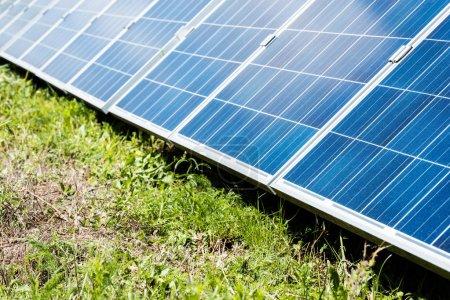 Photo pour Batteries d'énergie solaire bleueavec l'espace de copie et l'herbe verte - image libre de droit