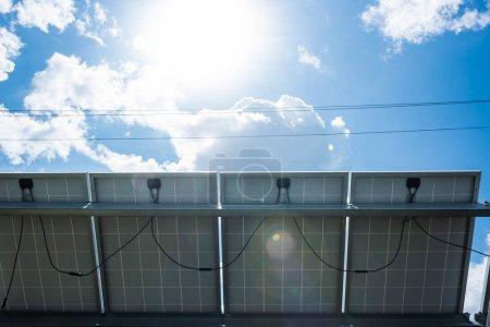 Photo pour Batteries d'énergie solaire bleues, soleil et ciel nuageux à l'extérieur - image libre de droit