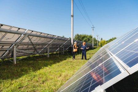 Foto de Ingeniero y empresaria hablando y caminando cerca de baterías de energía solar - Imagen libre de derechos