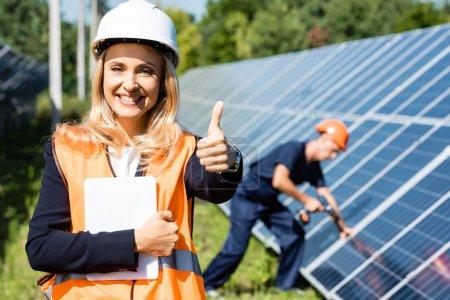 Foto de Atractiva empresaria en hardhat mostrando pulgar hacia arriba y sosteniendo la tableta digital - Imagen libre de derechos