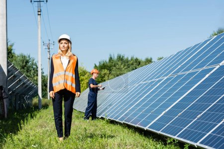 Photo for Attractive businesswoman in hardhat walking near solar energy batteries - Royalty Free Image