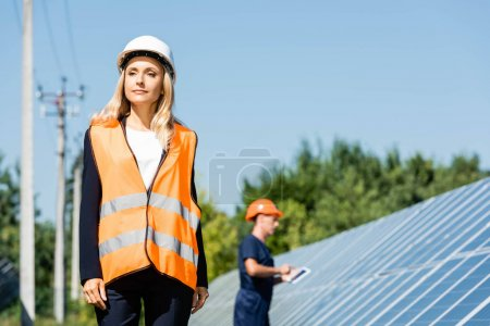 Photo for Attractive businesswoman in hardhat and safety vest looking away - Royalty Free Image