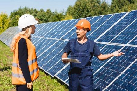 Photo pour Beau ingénieur et femme d'affaires parler et regarder les uns les autres - image libre de droit