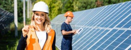 Foto de Plano panorámico de atractiva mujer de negocios en hardhat sonriendo y mostrando gesto de idea - Imagen libre de derechos