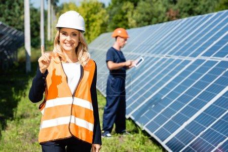 Photo pour Femme d'affaires attirante dans le sourire de casque et montrant le geste d'idée - image libre de droit
