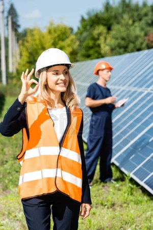 attractive businesswoman in hardhat smiling and showing ok gesture