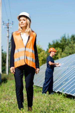 Foto de Atractiva empresaria en hardhat caminando y mirando hacia otro lado - Imagen libre de derechos