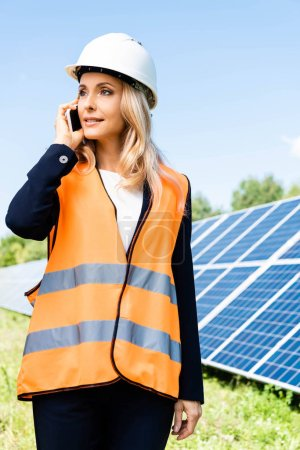 Photo for Attractive businesswoman in hardhat and safety vest talking on smartphone - Royalty Free Image