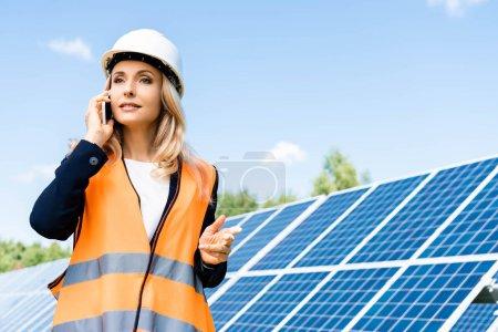 Foto de Atractiva mujer de negocios en hardhat y chaleco de seguridad hablando en el teléfono inteligente - Imagen libre de derechos