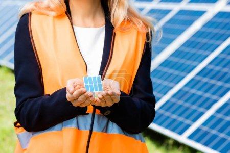 Foto de Recortado vista de la mujer de negocios en chaleco de seguridad celebración de modelo de batería solar - Imagen libre de derechos