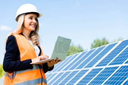businesswoman in safety vest and hardhat smiling and using laptop