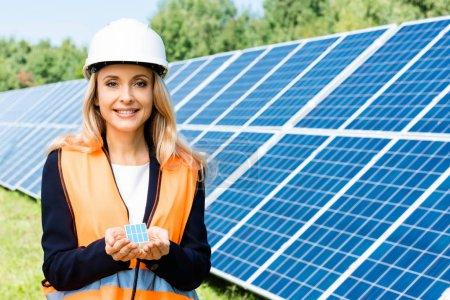 Photo pour Tir panoramique d'une femme d'affaires en gilet de sécurité tenant le modèle de batterie solaire - image libre de droit
