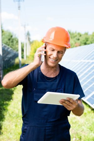 Photo for Handsome engineer in t-shirt and orange hardhat smiling and talking on smartphone - Royalty Free Image