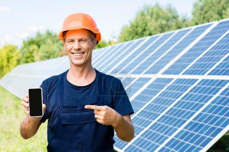 Photo pour Beau ingénieur en t-shirt et hardhat orange souriant et pointant avec le doigt au smartphone - image libre de droit