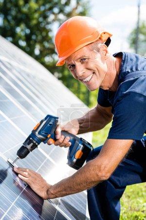 Foto de Ingeniero guapo en camiseta y naranja hardhat sonriendo y utilizando el taladro - Imagen libre de derechos