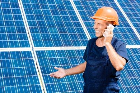 Foto de Ingeniero guapo en camiseta y naranja hardhat sonriendo y hablando en el teléfono inteligente - Imagen libre de derechos