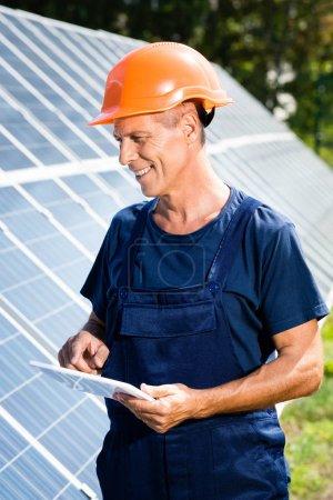 Foto de Ingeniero guapo en camiseta y naranja hardhat sonriendo y sosteniendo tableta digital - Imagen libre de derechos