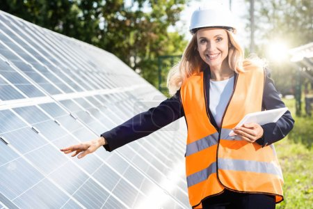 businesswoman in safety vest and hardhat smiling and holding digital tablet