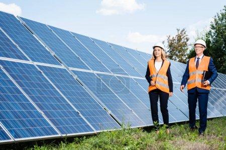 Photo pour Beau homme d'affaires et femme d'affaires attirantmarchant près des batteries d'énergie solaire - image libre de droit