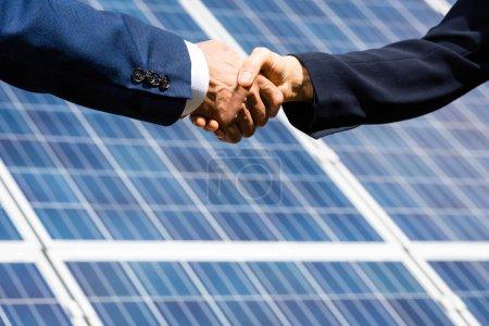 Photo pour Vue recadrée de l'homme d'affaires et femme d'affaires serrant la main à l'extérieur - image libre de droit