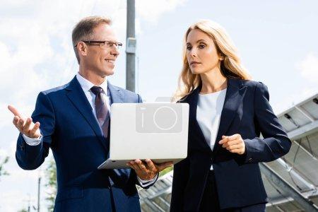 Photo pour Homme d'affaires beau et femme d'affaires attirante parlant et retenant l'ordinateur portatif - image libre de droit