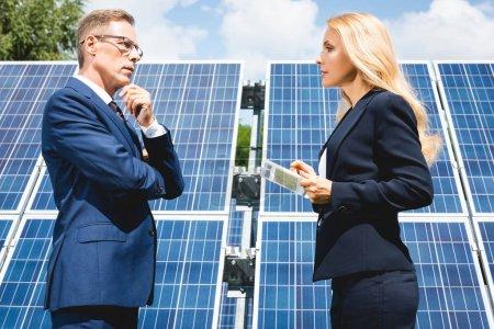 Foto de Vista lateral de apuesto hombre de negocios y empresaria hablando y sosteniendo la tableta digital - Imagen libre de derechos