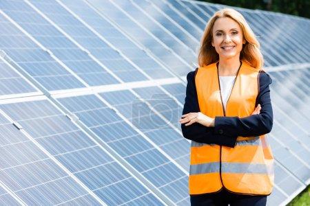 Foto de Atractiva mujer de negocios con brazos cruzados sonriendo y mirando a la cámara - Imagen libre de derechos