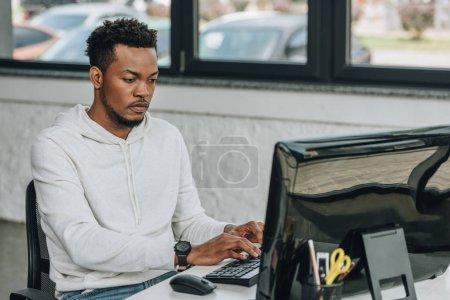 Photo pour Beau programmeur américain africain travaillant sur l'ordinateur dans le bureau - image libre de droit