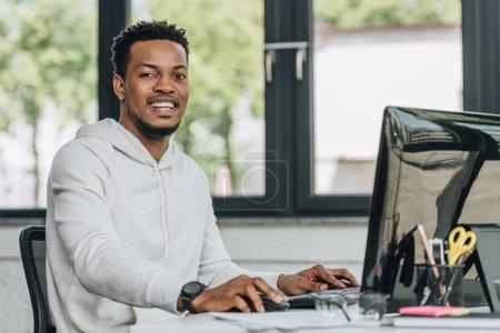 Photo pour Programmeur afro-américain joyeux regardant la caméra tout en travaillant sur l'ordinateur dans le bureau - image libre de droit