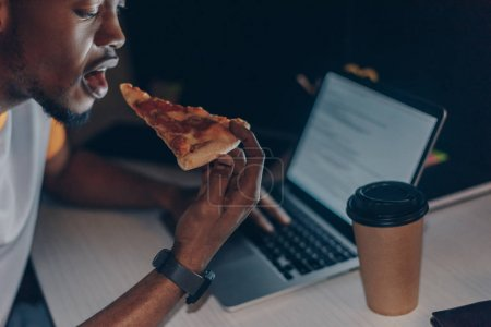 Photo for Young african american programmer eating pizza while sitting at workplace - Royalty Free Image