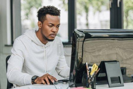 Photo pour Programmeur américain africain attentif travaillant sur l'ordinateur dans le bureau - image libre de droit