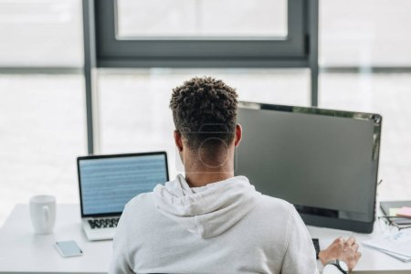 Photo for Back view of african american programmer working on computers in office - Royalty Free Image