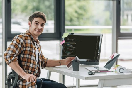 Photo pour Programmeur joyeux souriant à la caméra tout en étant assis près de l'écran de l'ordinateur avec script à l'écran - image libre de droit