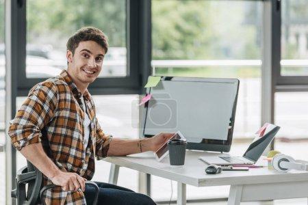 Photo pour Programmeur heureux souriant à l'appareil-photo tout en s'asseyant près du moniteur d'ordinateur dans le bureau - image libre de droit