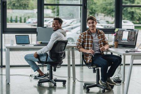 Photo pour KYIV, UKRAINE - 29 JUILLET 2019 : jeune programmeur assis près de l'écran de l'ordinateur avec Linkedin site Web à l'écran près d'un collègue afro-américain - image libre de droit
