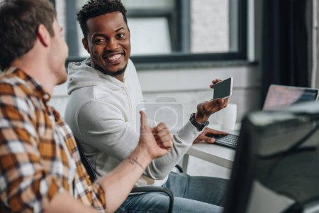 Photo for Selective focus of smiling african american programmer holding smartphone while sitting near colleague showing thumb up - Royalty Free Image