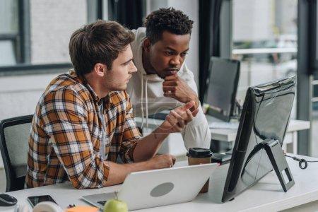 Photo pour Programmeur grave gestuelle tout en regardant moniteur d'ordinateur avec un collègue afro-américain - image libre de droit
