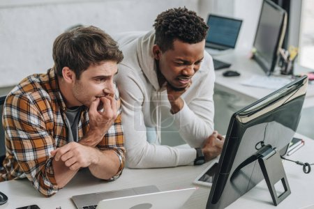 Foto de Dos programadores multiculturales preocupados mirando portátil en la oficina - Imagen libre de derechos
