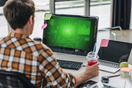 Photo pour Vue arrière du jeune programmeur retenant le verre de jus tout en s'asseyant au lieu de travail près du moniteur d'ordinateur avec des graphiques et des diagrammes sur l'écran - image libre de droit