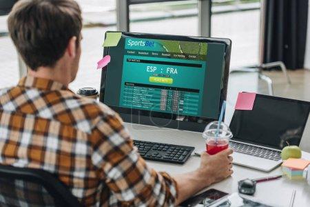 Photo pour KYIV, UKRAINE - 29 JUILLET 2019 : vue arrière du jeune programmeur tenant un verre de jus tout en étant assis sur le lieu de travail près de l'écran de l'ordinateur avec le site Web Sportsbet à l'écran - image libre de droit