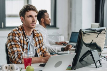 Photo for Thougtful programmer looking up while working near african american colleague - Royalty Free Image