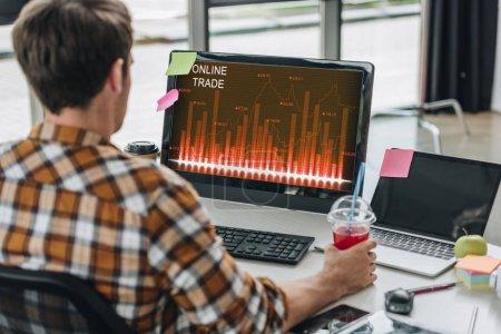 Photo pour Vue arrière du jeune programmeur tenant un verre de jus tout en étant assis sur le lieu de travail près de l'écran de l'ordinateur avec le commerce en ligne à l'écran - image libre de droit