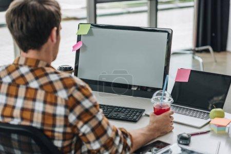 Photo pour Vue arrière du jeune programmeur retenant le verre de jus tout en s'asseyant au lieu de travail - image libre de droit