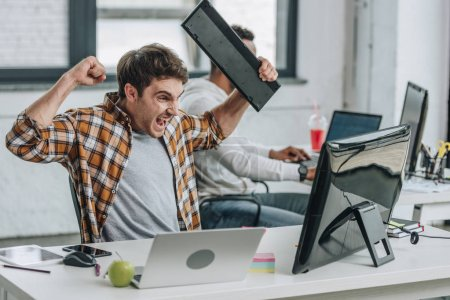 Photo for Irritated programmer holding keyboard and gesturing while looking at computer monitor - Royalty Free Image
