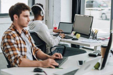Photo pour Foyer sélectif du programmeur afro-américain dans les écouteurs assis sur le lieu de travail près de collègue - image libre de droit