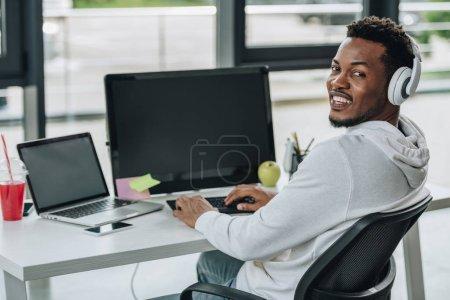 Photo pour Programmeur américain africain gai regardant l'appareil-photo tout en s'asseyant au lieu de travail - image libre de droit